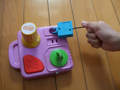 這組玩具模擬的日常生活原件包括開瓶蓋 (黃色物件)、插插頭 (藍色物件)以及拔浴缸塞子 (綠色物件)